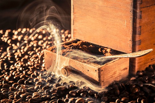 Freshly ground coffee and an old coffee grinder