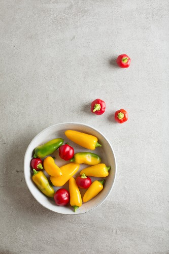 Red, yellow and green mini peppers in a bowl and next to it