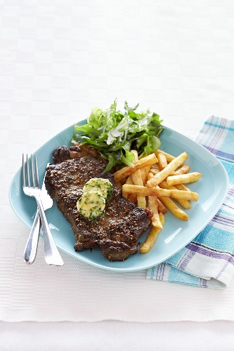 Peppered steak with herb butter, chips and salad
