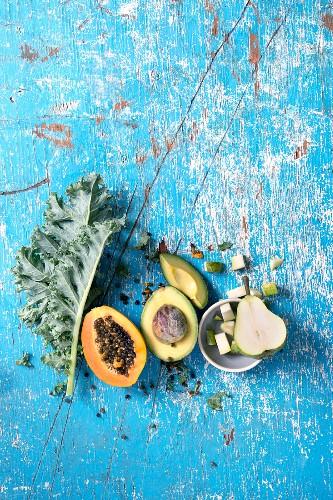 Still life with kale, papaya, avocado and pear