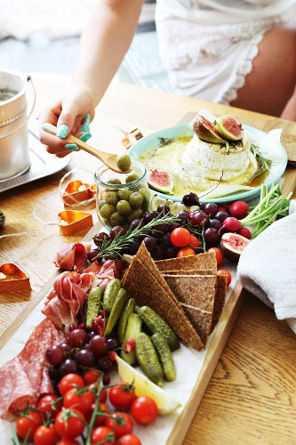 Baked Camembert with rosemary, honey and fresh figs and assorted cold cuts with vegetables and grapes
