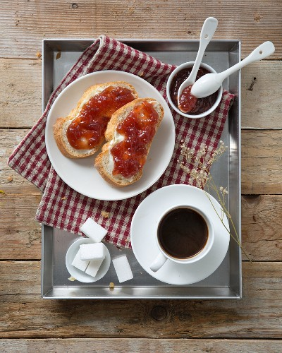Cup of coffee and bread and jam on a breakfast tray (seen from above)