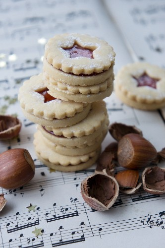 Jam sandwich biscuits with hazelnuts on a piece of sheet music