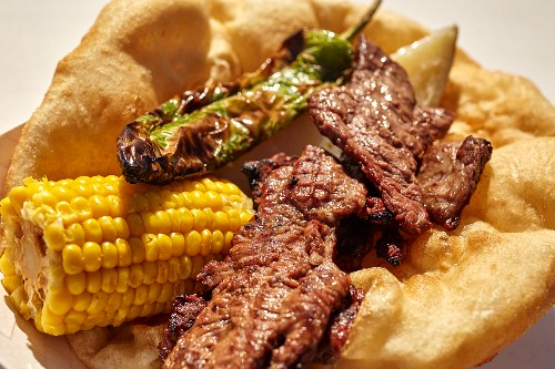 Fry bread (USA) with grilled mutton, corn cobs and chilli