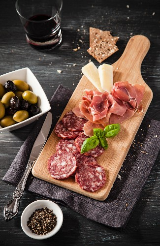 Salami, ham and cheese on a supper board served with olives and red wine
