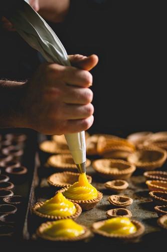 Shortcrust tartlets being filled with vanilla cream