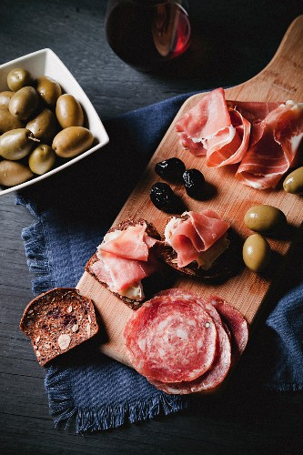 An open salami sandwich and an open ham and cheese sandwich on a supper board served with olives and wine