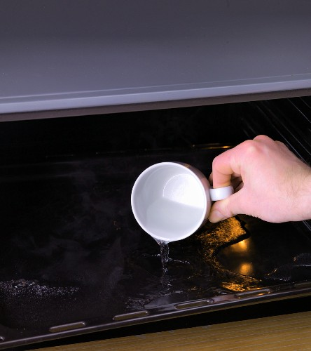 A cup of water being poured on to a hot baking tray for steaming
