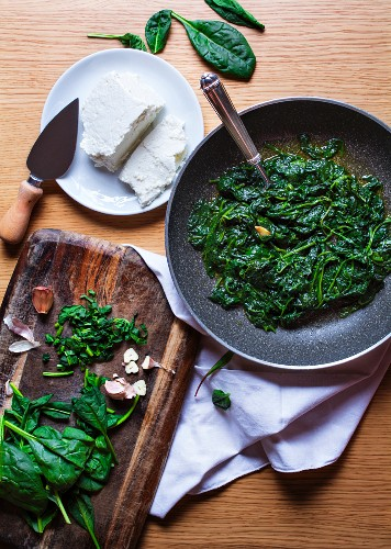 Steamed spinach with ricotta and garlic being made