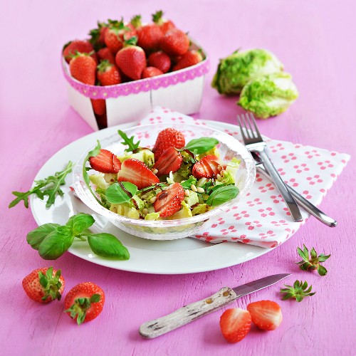 A salad with strawberries, a punnet of strawberries and lettuce in the background
