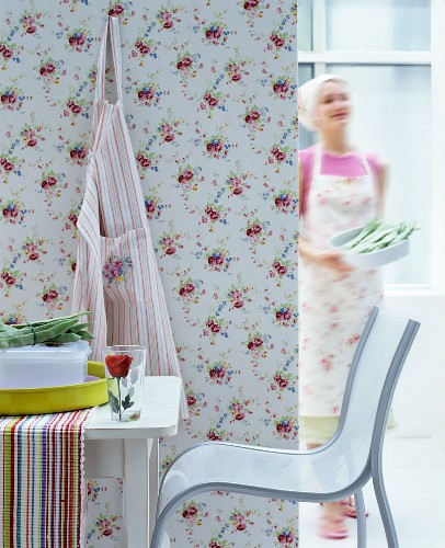 Modern chair and table in front of partition with floral wallpaper; woman wearing apron and headscarf in background