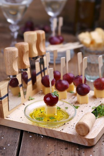 Cheese appetizers with grapes on a wooden chopping board