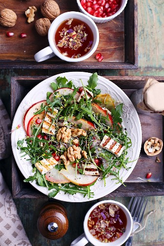 Rocket fired with walnuts and grilled tofu with cups of tea and pomegranate seeds