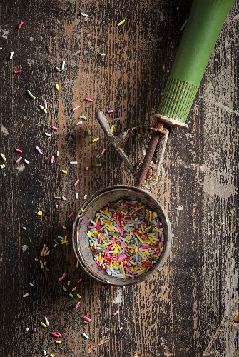 An old ice cream scoop with a green handle filled with colourful sugar sprinkles on a wooden surface