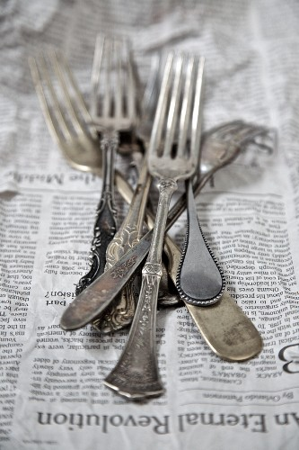 Vintage silver forks on a newspaper