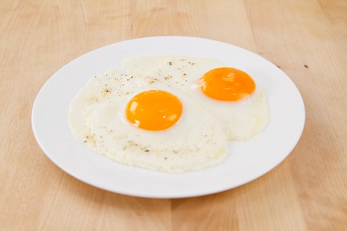 Two Over Easy Eggs on a Plate; Fork and Bottle of Tabasco