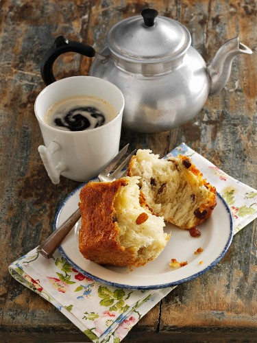 A baked, sweet yeast dumpling and coffee