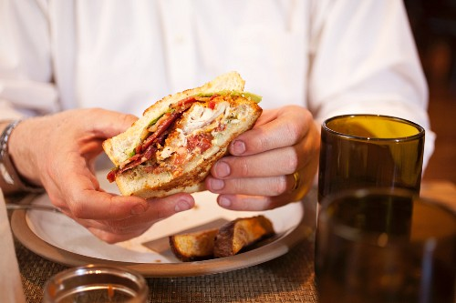 Person Eating a Fried Catfish BLT in Husk Restaurant in South Carolina