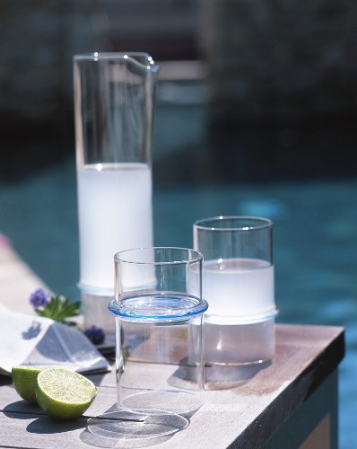 An aperitif in a jug and glasses on table in the open air