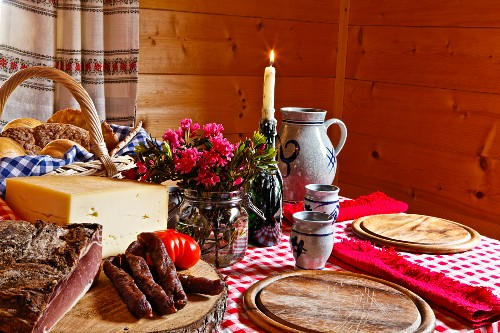 Marende (South Tyrolean supper) in a farmhouse dining room with bacon, sausage, cheese, bread and wine