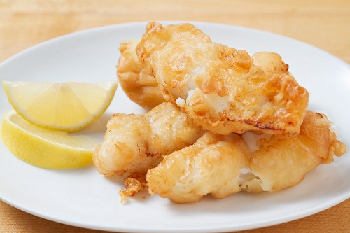 Battered fish fillets with lemon wedges