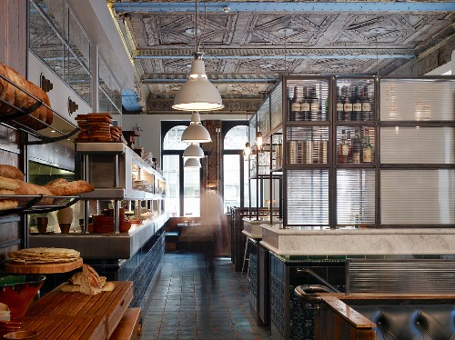 English restaurant in historic hall with ornamented ceiling and old counters with modern steel and glass shelving on marble slabs