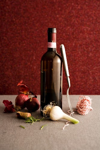 Open bottle of red wine with ingredients & cooking utensils
