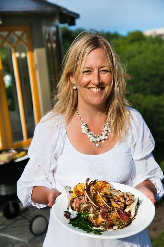 Blonde woman holding plate of grilled lamb chops, artichokes and lemons