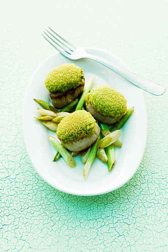 Pork fillet with a herb wasabi crust on a bed of spring onion