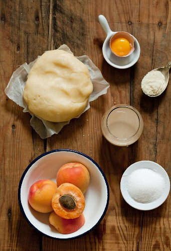 Ingredients for apricot cake (short pastry, apricots, sugar, egg yolk, flour)