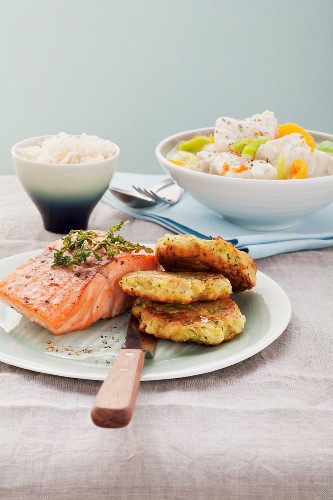 Salmon fillet with zucchini puffers, fish dish in the background