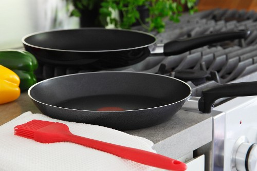 Two non-stick pans and a silicon brush