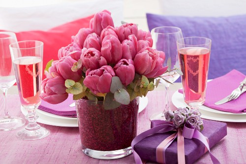 Festive table with tulips, present and rosé sparkling wine