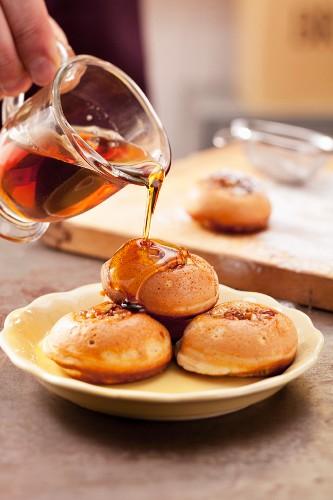 Aebleskiver (Gefüllte Pancakes) mit Ahornsirup begiessen