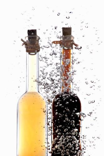 Essig- und Ölflasche im Wasser mit Luftbläschen