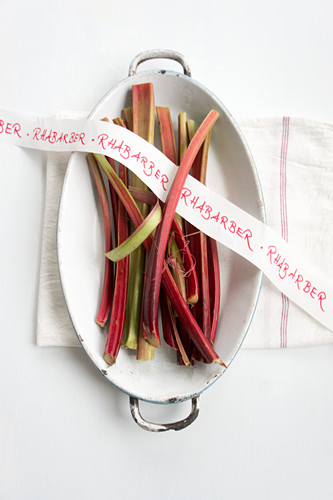 Rhubarb stems and ribbon with writing in a casserole dish