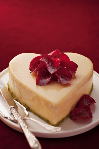 A heart-shaped cake decorated with rose petals for Valentines Day