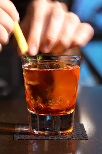 Person Adding Garnish to a Glass of Negroni Sbagliato