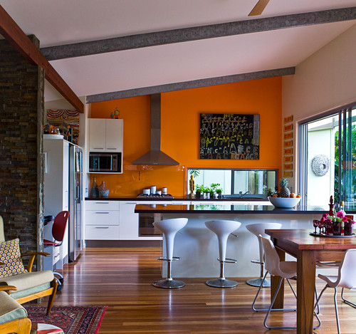 A spacious kitchen with a bright orange wall and a shiny kitchen counter with designer chairs