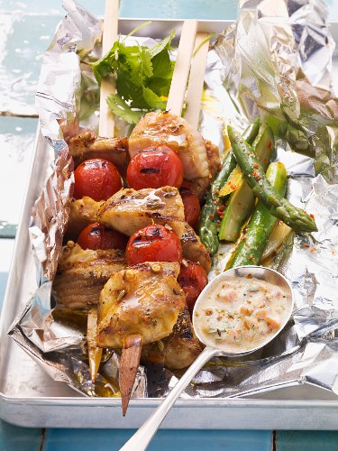 Grilled wels catfish and tomato kebabs with green asparagus and spicy yogurt dip