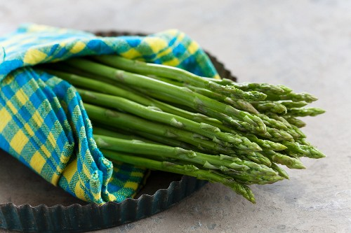 Green Thai asparagus wrapped in a napkin on a baking tray