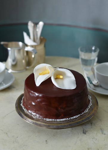 An almond and chocolate cake decorated with calla lilies