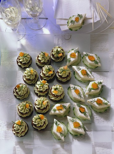 Pumpernickel Coins with Nut Mousse and Trout Mousse and Cucumber Slices with Salmon Mousse and garnished with Caviar