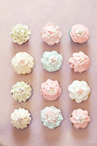 Various cupcakes topped with frosting and sugar flowers