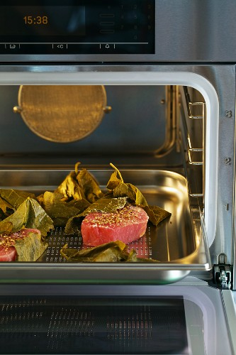 Tuna fillets with coriander and vine leaves being prepared in a steamer