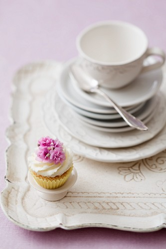 A cupcake on a tray with a stack of plates and a teacup