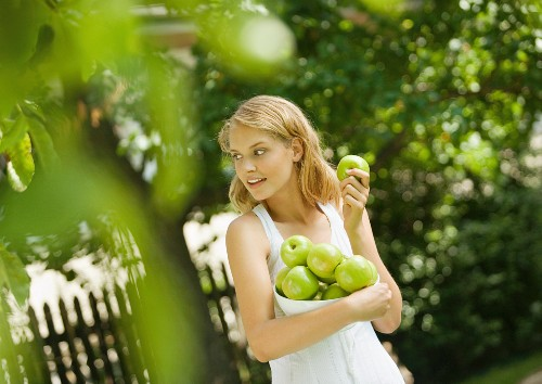 Young woman wearing white dress, holding bowl of apples