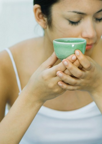 Woman holding up tea cup, eyes closed