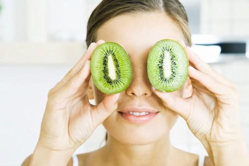 Woman holding two kiwi halves up to her eyes like binoculars, headshot