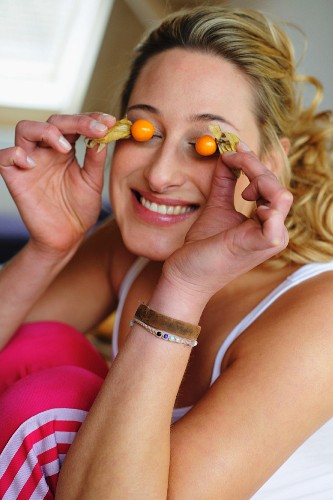 Young woman covering her eyes with fruit